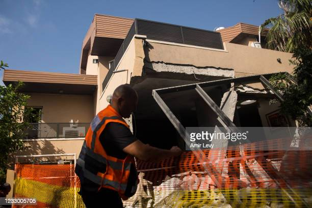 Rescue team work at s house where a rocket fired from the Gaza Strip hit on May 20, 2021 in Ashkelon, Israel. The Hamas-run health ministry in Gaza...