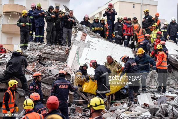 Rescue teams and firefighters carry a victim found under the rubble of a collapsed building in the town of Durres, western Albania on November 28...
