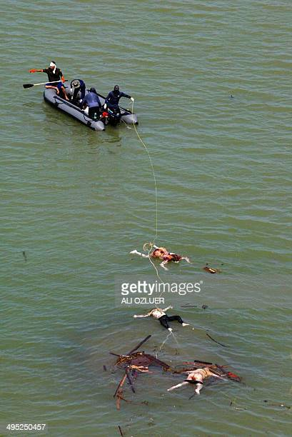 Rescue teams attach a rope to corpses in the southeastern sea resort of Khao Lak in Thailand 28 December 2004 The confirmed death toll from the...