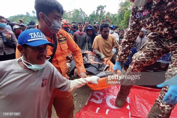 Rescue teams carry the body of a miner after an illegal gold mine collapsed killing at least three people, with more believed to be buried under the...