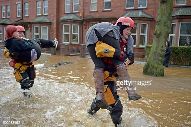 Rescue teams carry two young women to safety through the flood water as they continue to to evacuate homes after Storm Desmond caused flooding on...
