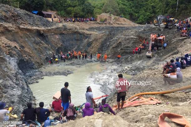 Rescue teams conduct a search for miners buried by a landslide at an illegal gold mining operation in the village of Buranga in Parigi Moutong...