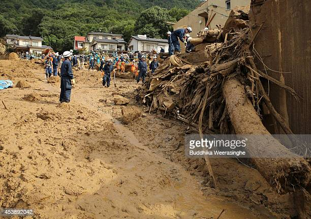 Rescue teams continue the search for missing people among the debris of houses destroyed by a landslide caused by torrential rain at the site of a...