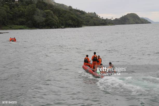 Rescue teams continue to search for victims at the Lake Toba ferry port in the province of North Sumatra early on June 19 after a boat overturned and...