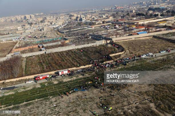 TOPSHOT Rescue teams gather at the scene after a Ukrainian plane carrying 176 passengers crashed near Imam Khomeini airport in the Iranian capital...