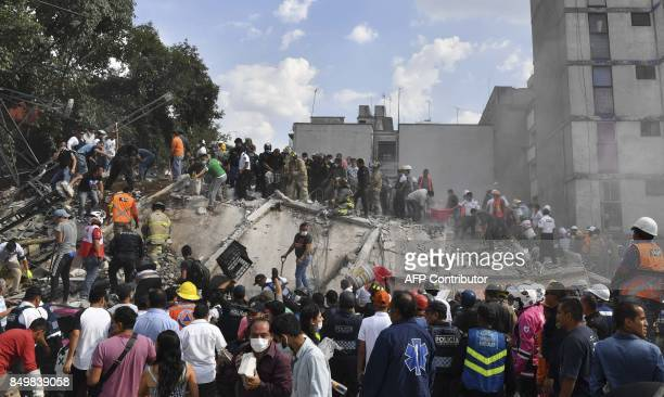 Rescue teams look for people trapped in the rubble after an earthquake in Mexico City on September 19 2017 A devastating quake in Mexico on Tuesday...