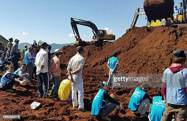 Rescue teams search for the bodies of miners killed in a landslide in a jade mining area in Hpakhant in Myanmar's Kachin state on November 24 2015...