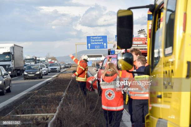 Rescue teams secure the accident site along the freeway A5 a fire fighter waves to the opposite lane in St LeonRot Germany 12 February 2018 At leas...
