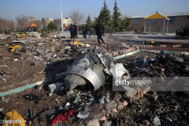 TOPSHOT Rescue teams work amidst debris after a Ukrainian plane carrying 176 passengers crashed near Imam Khomeini airport in the Iranian capital...