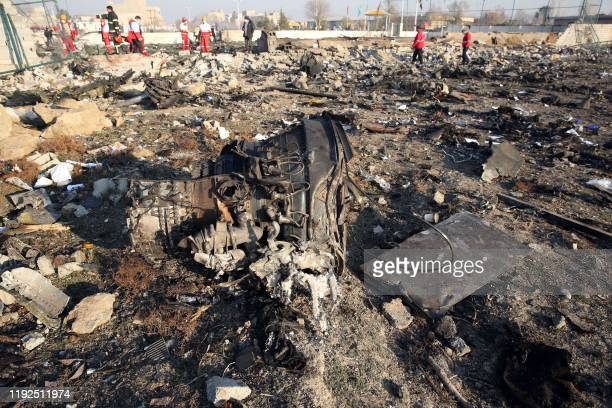 TOPSHOT Rescue teams work at the scene after a Ukrainian plane carrying 176 passengers crashed near Imam Khomeini airport in the Iranian capital...