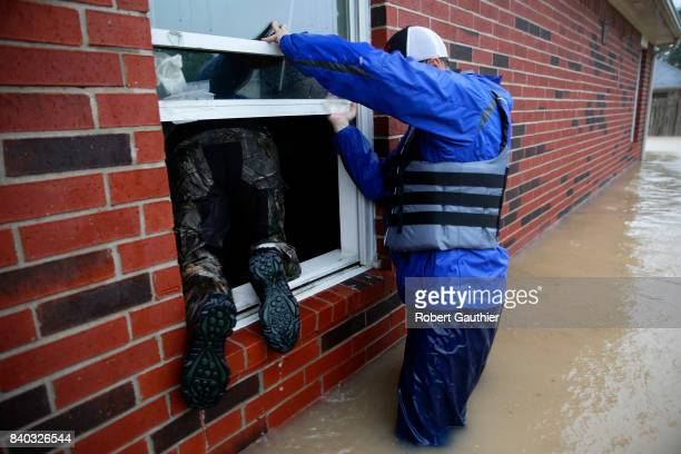 Rescue volunteer Jan Tullos climbs through a window as Steven Andersen helps in search of an injured woman who was reportedly stranded inside this...