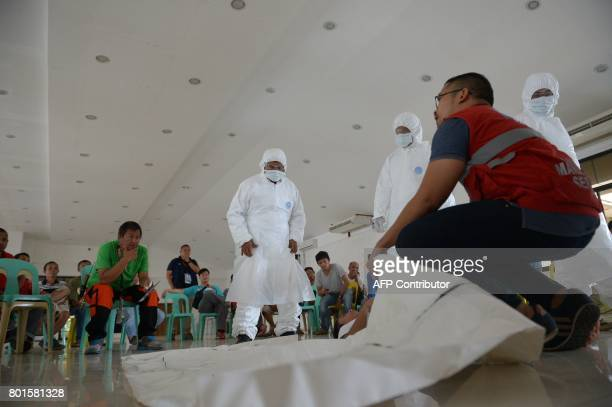 Rescue volunteers take a crash course on cadaver handling given by International Red Cross members in preparation for the retrieval of bodies from...