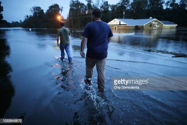 Rescue volunteers wade in water while looking for a way around Highway 70 where the Neuse River had flooded the road September 15, 2018 in Kinston,...