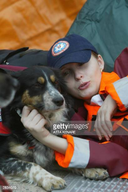 A rescue woman of Slovakia rests along with her sniff dog in the devastated southeastern Iranian city of Bam 28 December 2003 The chances of finding...