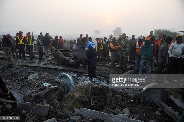 Rescue worker and onlookers stand near the wreckage of the train on the damaged tracks where a train derailed near Pukhrayan in Kanpur district on...