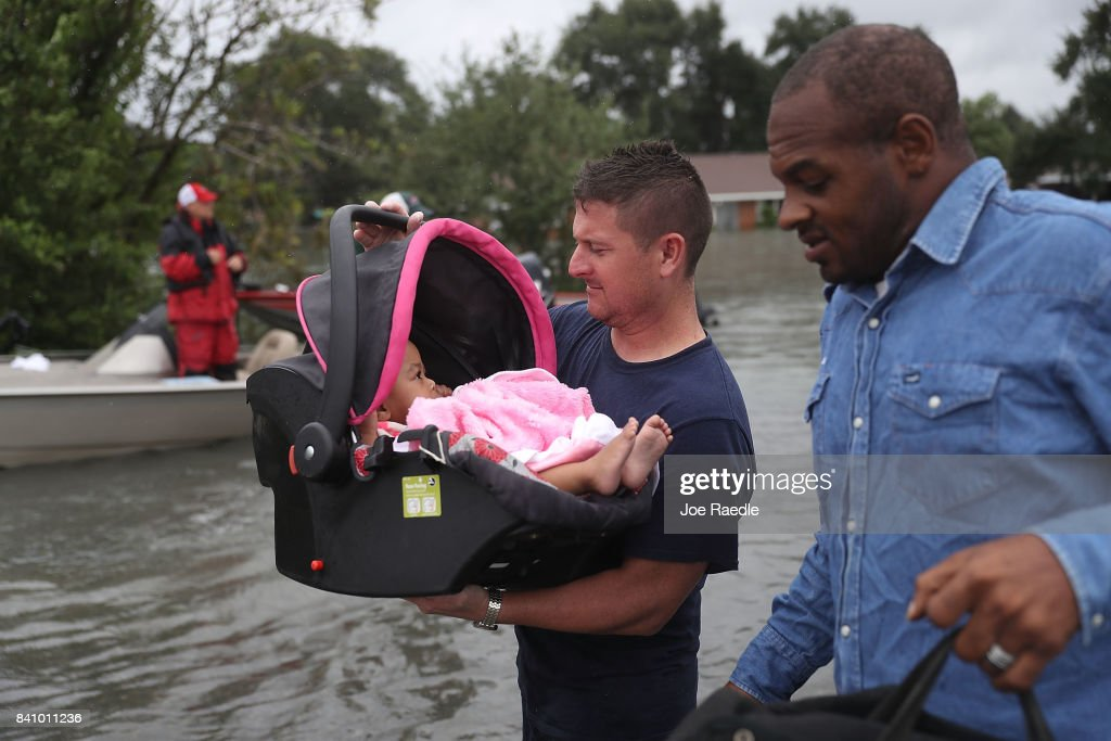 A rescue worker carries a baby to dry land after she was rescued from the flooding of Hurricane Harvey on August 30, 2017 in Port Arthur, Texas. Harvey, which made landfall north of Corpus Christi late Friday evening, is expected to dump upwards to 40 inches of rain in Texas over the next couple of days.