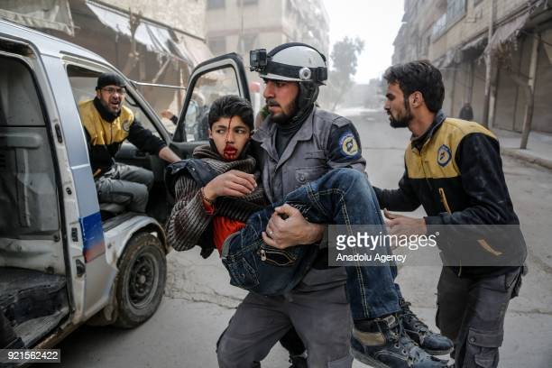 A rescue worker carries a boy who was saved alive inside the debris of buildings after Assad Regime carried out an airstrike over Sakba town of...