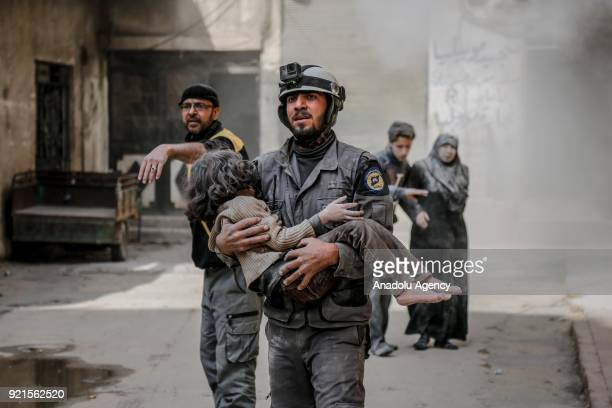 A rescue worker carries a girl who was saved alive inside the debris of buildings after Assad Regime carried out an airstrike over Sakba town of...