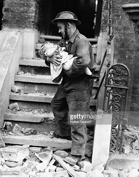 A rescue worker carries a toddler to safety after her home was damaged in an air raid