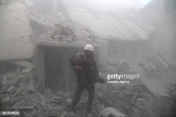 A rescue worker carries a woman who was saved alive inside the debris of buildings after Assad Regime carried out an airstrike over Arbin town of the...