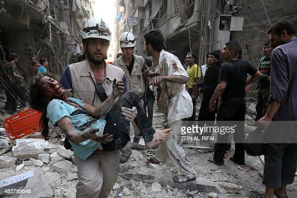 A rescue worker carries a wounded girl following a reported air strike by Syrian government forces on July 27 2014 in the northern city of Aleppo...