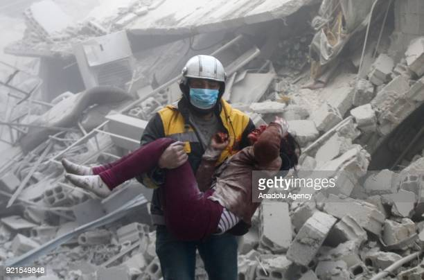 A rescue worker carries a wounded young woman who was saved alive inside the debris of buildings after Assad Regime carried out an airstrike over...
