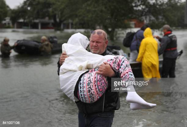 A rescue worker carries an evacuee to dry land after she was rescued from the flooding of Hurricane Harvey on August 30 2017 in Port Arthur Texas...