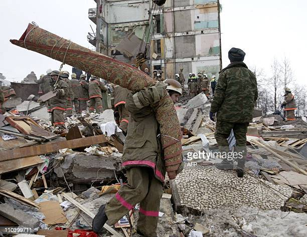 A rescue worker cleans the debris of an appartment building which collapsed after an explosion in the northern Russian town of Arkhangelsk 16 March...