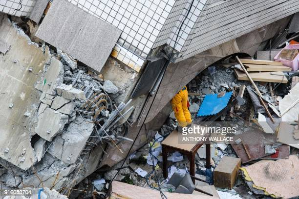 TOPSHOT A rescue worker clears debris to make way for the recovery of the dead bodies of a Hong Kong Canadian couple from the Yun Tsui building which...