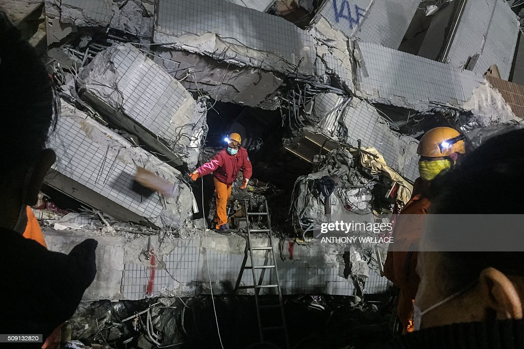 TOPSHOT - A rescue worker (C) discards an object as he searches through rubble for belongings for relatives (L and R) to help identify from the remains of a building which collapsed in the 6.4 magnitude earthquake, in the southern Taiwanese city of Tainan early on February 9, 2016. Rescuers deployed heavy machinery on February 9 in a renewed effort to locate more than 100 people trapped in the rubble of a Taiwan apartment complex felled by an earthquake as the 72-hour 'golden window' for finding survivors passed.