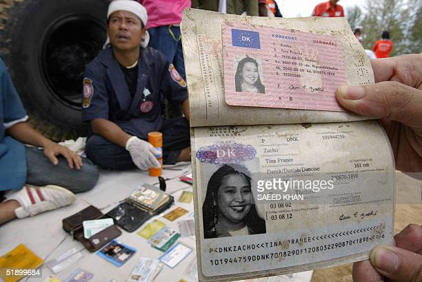 A rescue worker displays the passport and ID of Danish national Tina Pranee Zacho after collecting them from the debris in Khao Lak 29 December 2004...