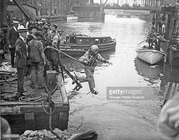 Rescue worker, dressed in a diving suit, leaps into the Chicago River at the site of the Eastland disaster, July 24, 1915. The passenger ship SS...
