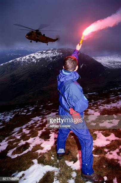 Rescue Worker Flashing Flare at Helicopter