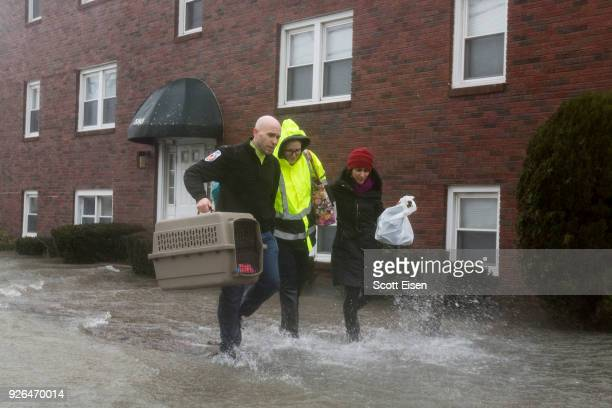 A rescue worker helps carry a rescued animal away from a flooded apartment building as the Hough's Neck area is flooded due to a strong coastal storm...
