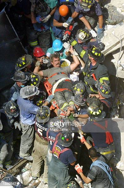 Rescue worker is pulled from the rubble of the World Trade Center September 13, 2001 in New York City two days after two hijacked airplanes slammed...