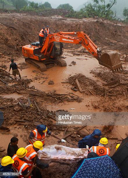 Rescue worker recovering a dead body as a JCB machine digs in swirling sludge to find way into dozens of submerged homes at the site of a landslide...