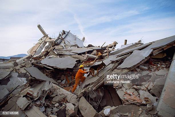 A rescue worker searches for people trapped in buildings wrecked by earthquake in the town of Lioni Italy