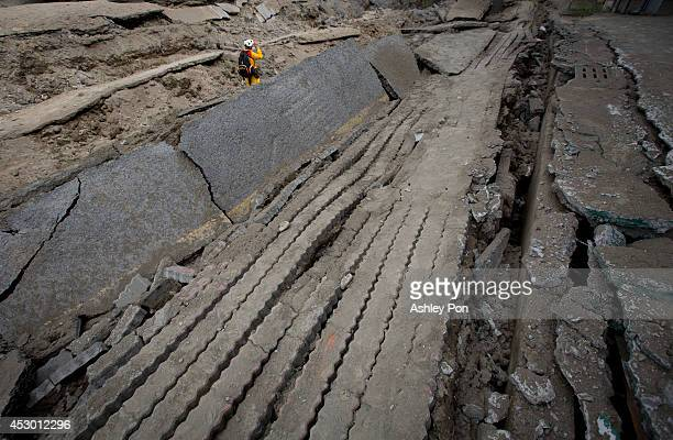Rescue worker searches through the site of the damaged road after several gas explosions took place in southern Kaohsiung on August 1, 2014 in...