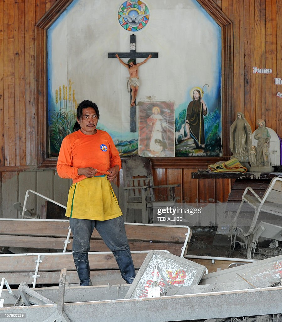 A rescue worker stands inside a church littered with debris swept in by flash floods caused by Typhoon Bopha in the village of Andap in the town of New Bataan in Compostela Valley province on December 8, 2012. Hungry and homeless typhoon survivors appealed for help on December 8 as the ravaged southern Philippines mourned its more than 500 dead and desperate people in one hard-hit town looted shops in search of food.