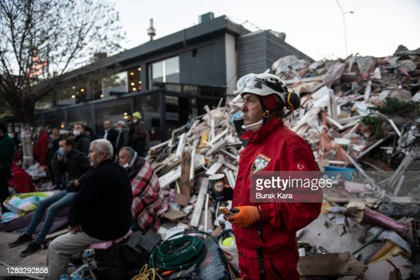 Rescue worker stands near a collapsed building as earthquake survivors wait for news of their loved ones after a powerful earthquake struck on...