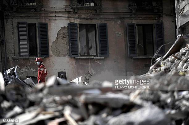A rescue worker stands on rubble on April 7 2009 in the center of the Abruzzo capital L'Aquila epicentre of an earthquake the day before Aftershocks...