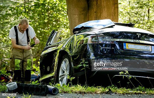 A rescue worker takes a picture around the spot where a Tesla slammed into a tree in Baarn on September 7 2016 Pioneering US electric car firm Tesla...