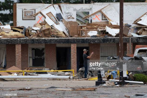 A rescue worker takes photos of the American Value Budget Inn May 26 2019 in El Reno Oklahoma At least two people were killed in this Oklahoma City...