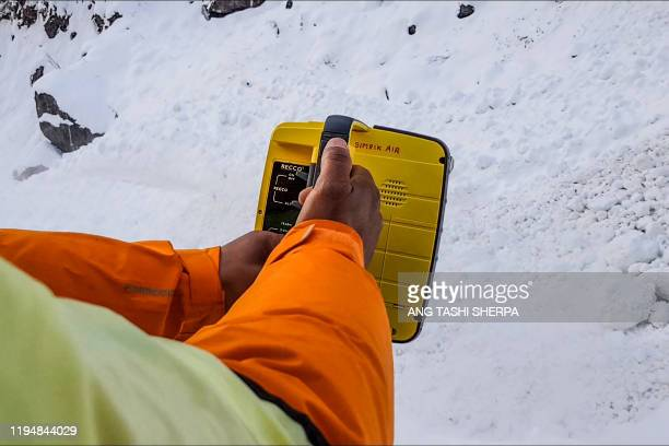 Rescue worker uses a machine to track missing trekkers on the avalanche site in Annapurna mountain region some 200 kms west of Kathmandu on January...