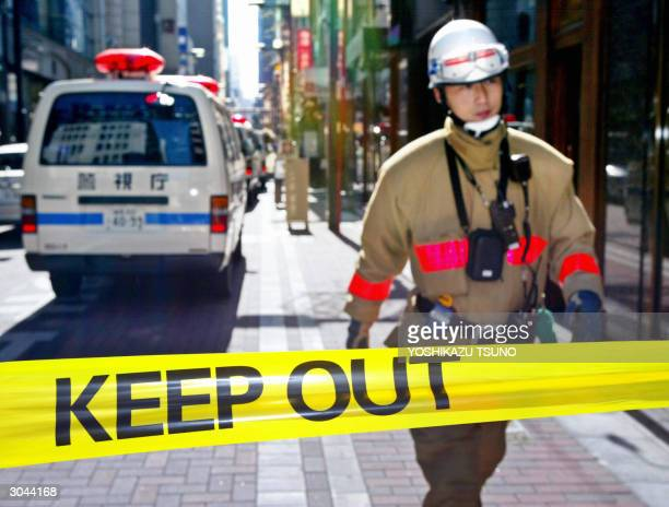 A rescue worker walks at keepout area at Tokyo's Ginza district 05 March 2004 after two men robbed a jewelry shop of 35 billion yen worth of...
