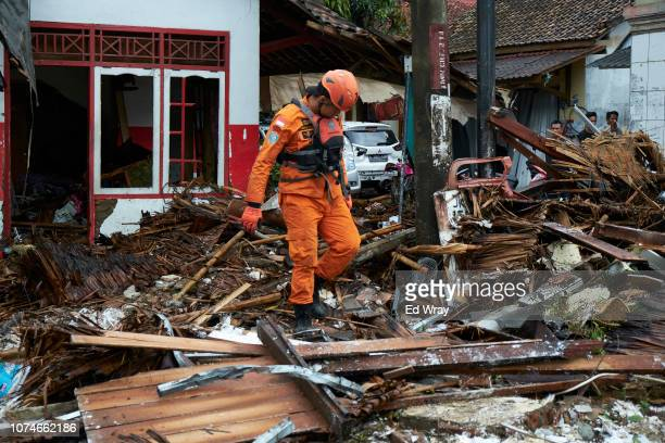 A rescue worker walks through the rubble from houses destroyed by a tsunami on December 23 2018 in Carita Indonesia Over 220 people have reportedly...