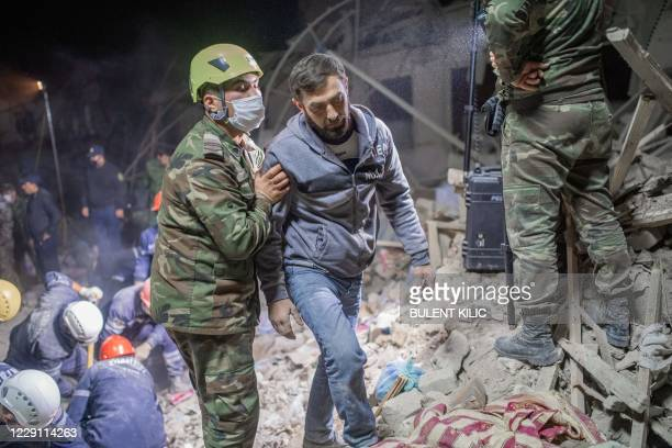 Rescue worker walks with a resident looking for relatives at a site hit by a rocket during fighting over the breakaway region of Nagorno-Karabakh, in...