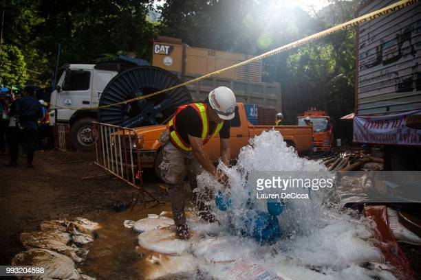 Rescue worker washes his hands in water pumped out of the cave on July 7, 2018 in Chiang Rai, Thailand. The 12 boys and their soccer coach have been...