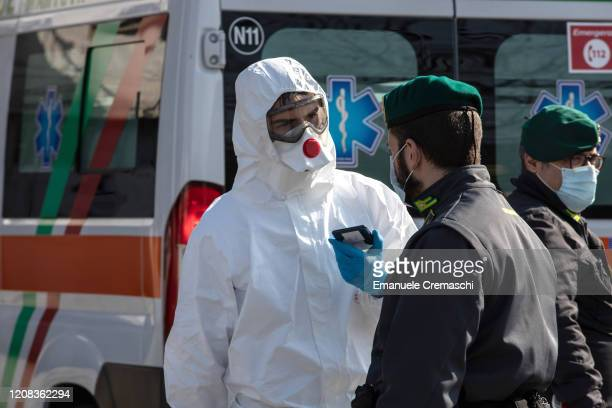 Rescue worker, wearing a protective suit, talks to an Italian Guardia di Finanza officer at a road block on February 24, 2020 in Casalpusterlengo,...