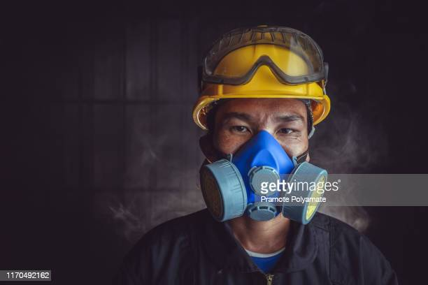 a rescue worker wears a respirator in a smokey, toxic atmosphere. image show the importance of protection readiness and safety in industrial factory. - air respirator mask stock pictures, royalty-free photos & images